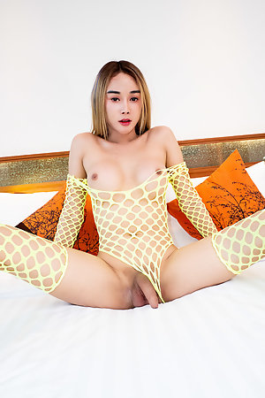Ladyboy Alice is wearing a bright yellow netted top with matching bra and panties.