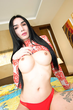 Slim and elegant Ladyboy Bella is wearing a sheer red and white dress.