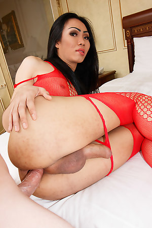 Tall and sexy Swan is leaning against the doorway with a sheer red body stocking clinging to her all-natural body.