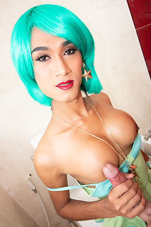 Slim Ladyboy Creamy is in the bathroom with wild colored hair and wearing a green blouse and stockings with a white mini skirt.