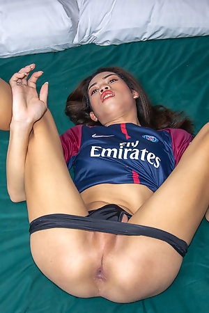 Natural Ladyboy Lee is wearing a tight football jersey and jean shorts.