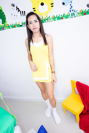 Ladyboy Lee is wearing a little yellow dress with white panties and socks.