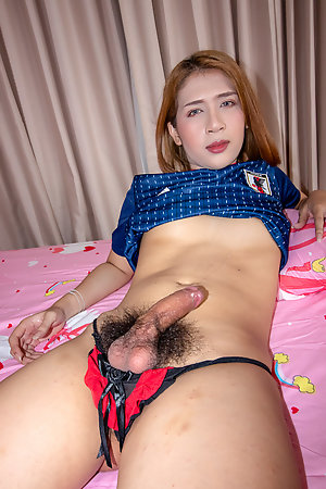 Ladyboy Bipor is wearing a football jersey tied up around her waist with black socks and panties.