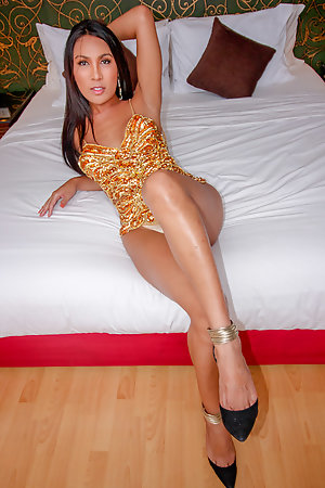 Ladyboy Emmy is wearing a gold dress and high heels.